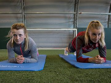 Female jockey and a female footballer doing a planking challenge.