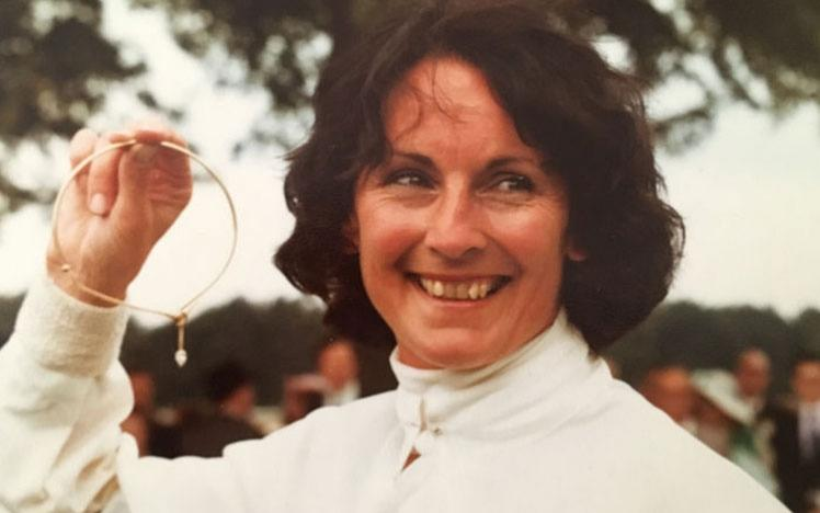 Female jockey holding a necklace in hand.